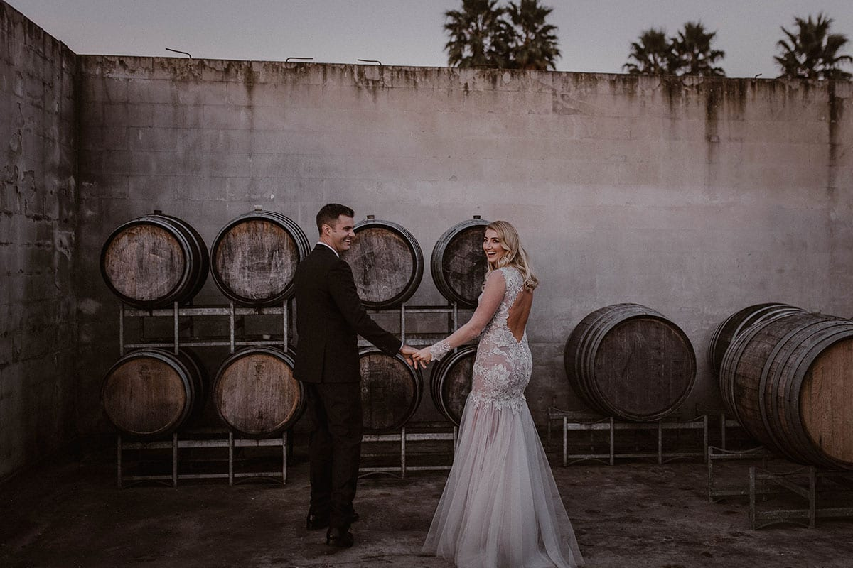 Real Weddings | Vinka Design | Real Brides Wearing Vinka Gowns | Rikki-Lee and Adam hold hands with wine barrels around, Rikki-Lee showing low back of bespoke gown