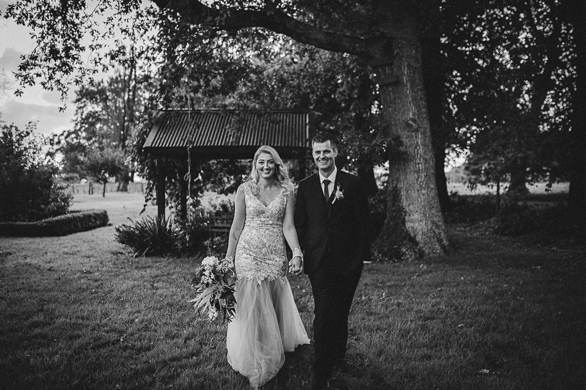 Real Weddings | Vinka Design | Real Brides Wearing Vinka Gowns | Rikki-Lee and Adam hold hands with Rikki-Lee in stunning bespoke wedding gown with beautiful lace detail long sheer sleeves with cuff detail and floaty chiffon layers at bottom of dress in black and white