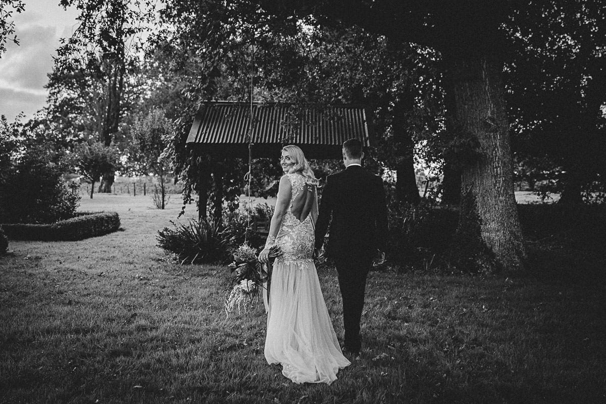 Real Weddings | Vinka Design | Real Brides Wearing Vinka Gowns | Rikki-Lee and Adam hold hands walking away with Rikki-Lee in stunning bespoke wedding gown with beautiful lace detail long sheer sleeves with cuff detail and floaty chiffon layers at bottom of dress into train and low exposed back in black and white