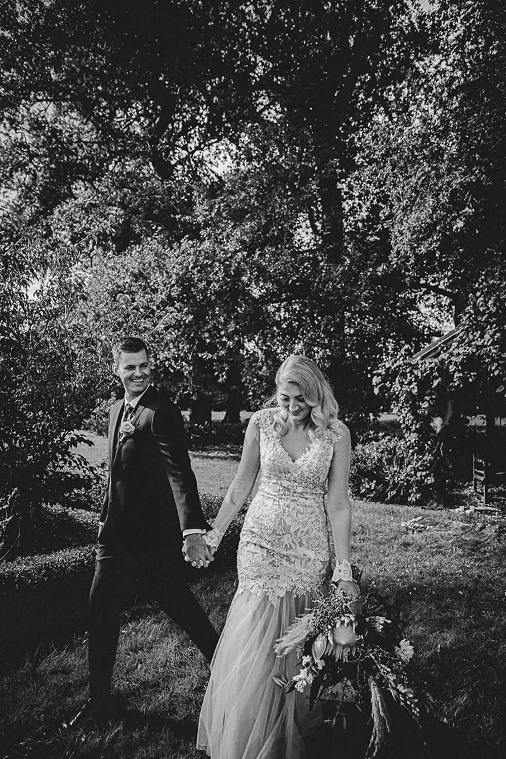 Real Weddings | Vinka Design | Real Brides Wearing Vinka Gowns | Rikki-Lee and Adam hold hands with Rikki-Lee in stunning bespoke wedding gown with beautiful lace detail long sheer sleeves with cuff detail and floaty chiffon layers at bottom of dress