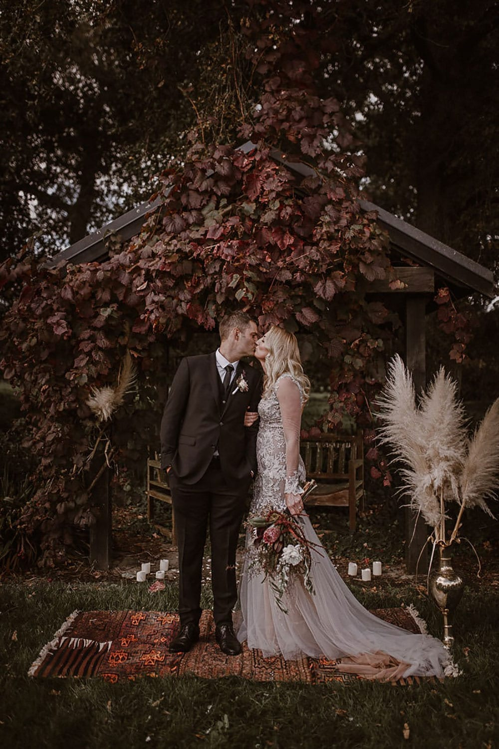 Real Weddings | Vinka Design | Real Brides Wearing Vinka Gowns | Rikki-Lee and Adam kiss under fall leaves with Rikki-Lee in stunning bespoke wedding gown with beautiful lace detail long sheer sleeves with cuff detail and floaty chiffon layers at bottom of dress
