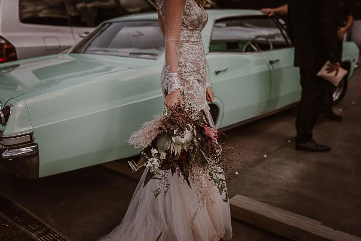 Real Weddings | Vinka Design | Real Brides Wearing Vinka Gowns | Rikki-Lee and Adam lower half of Rikki-Lee in stunning bespoke wedding gown with beautiful lace detail long sheer sleeves with cuff detail and floaty chiffon layers at bottom of dress