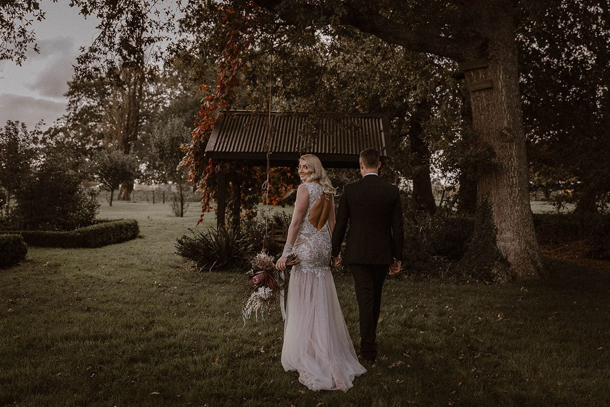 Real Weddings | Vinka Design | Real Brides Wearing Vinka Gowns | Rikki-Lee and Adam walking away Rikki-Lee looking over should showing back of dress detail with chiffon layers and low back