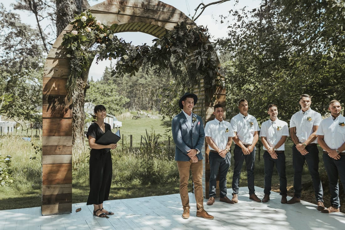 Real Weddings | Vinka Design | Real Brides Wearing Vinka Gowns | Briar and Corey ceremony under archway in gardens with groomsmen waiting for bride