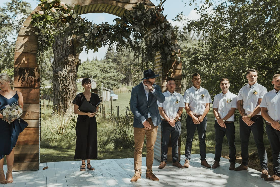 Real Weddings | Vinka Design | Real Brides Wearing Vinka Gowns | Briar and Corey ceremony under archway in gardens with groomsmen