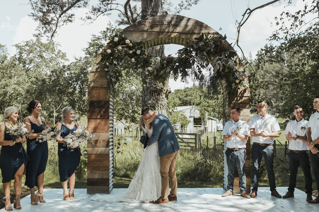 Real Weddings | Vinka Design | Real Brides Wearing Vinka Gowns | Briar and Corey kissing in archway in gardens