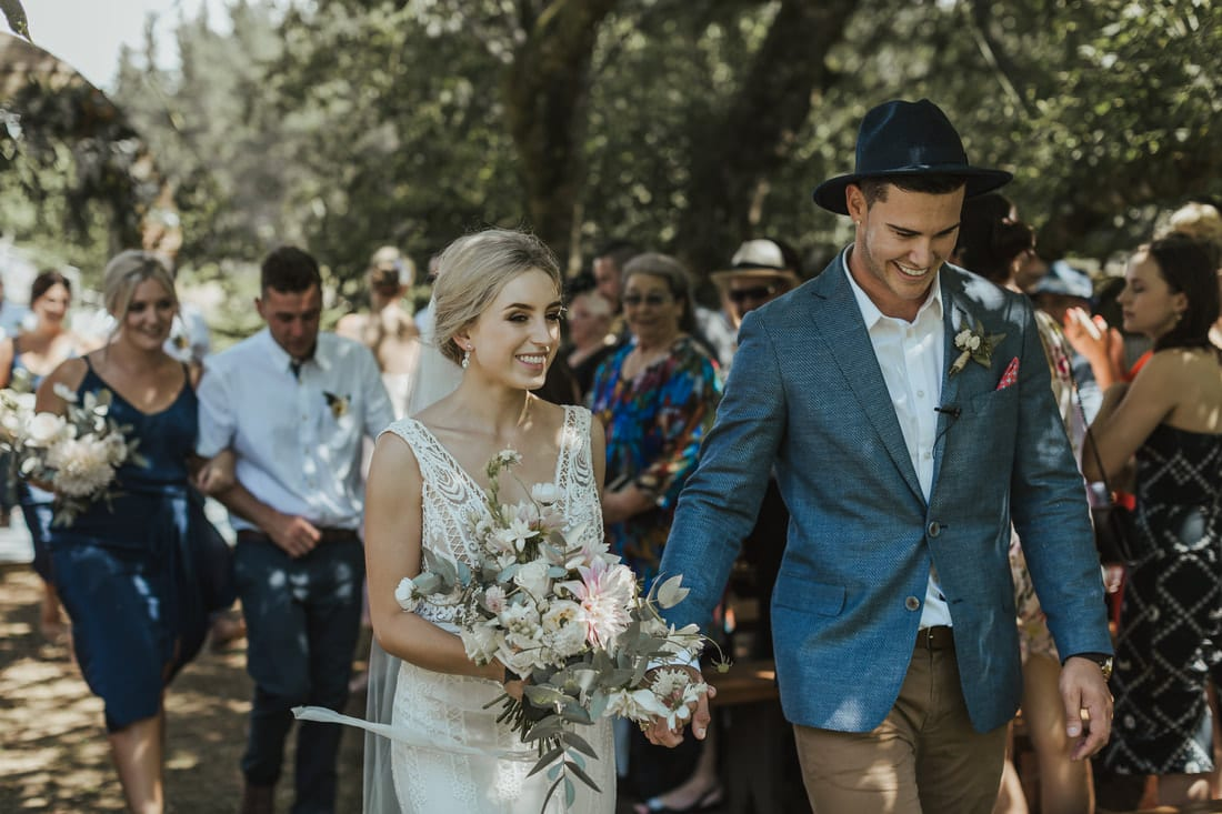Real Weddings | Vinka Design | Real Brides Wearing Vinka Gowns | Briar and Corey holding hands walking down aisle bespoke gown lace detail