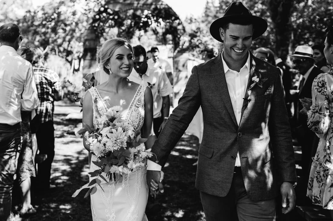 Real Weddings | Vinka Design | Real Brides Wearing Vinka Gowns | Briar and Corey holding hands bespoke gown lace detail black and white