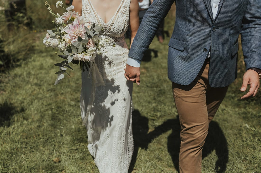 Real Weddings | Vinka Design | Real Brides Wearing Vinka Gowns | Briar and Corey lower half holding hands bespoke gown lace detail