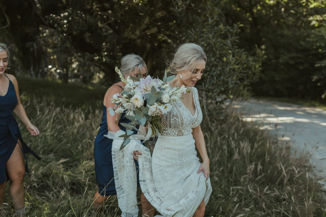 Real Weddings | Vinka Design | Real Brides Wearing Vinka Gowns | Briar and Corey - walking through field dress being help and front v detail showing