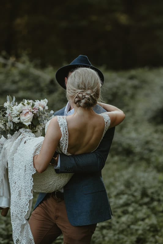 Real Weddings | Vinka Design | Real Brides Wearing Vinka Gowns | Briar and Corey in arms with low back of bespoke wedding dress on show