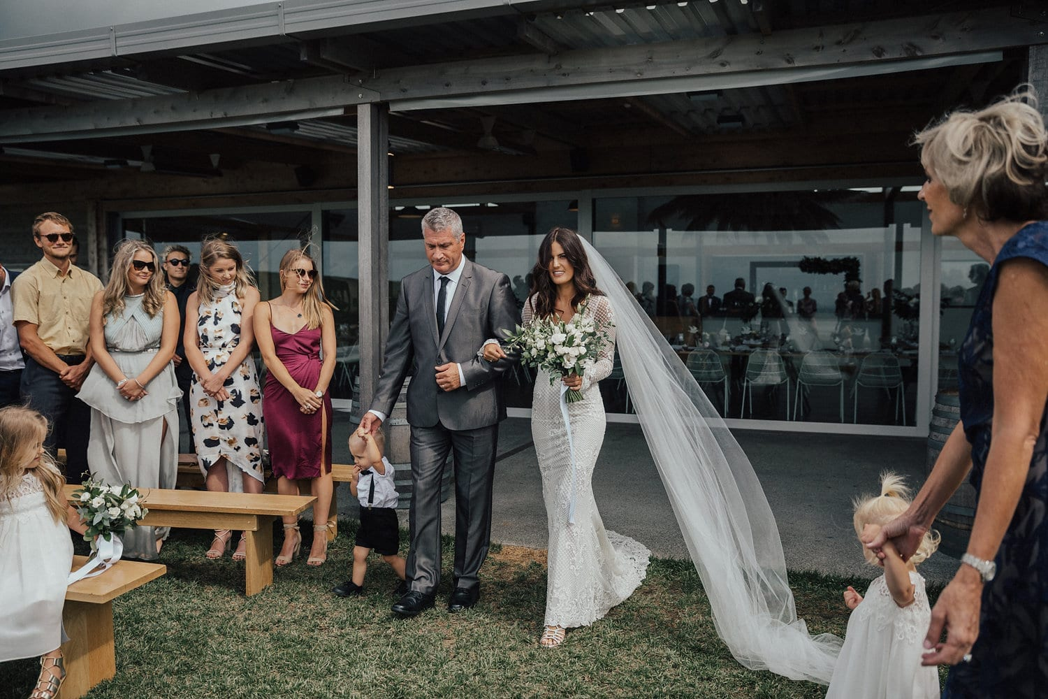 Real Weddings | Vinka Design | Real Brides Wearing Vinka Gowns | Nicole and Hayden - Nicole walking down aisle with veil
