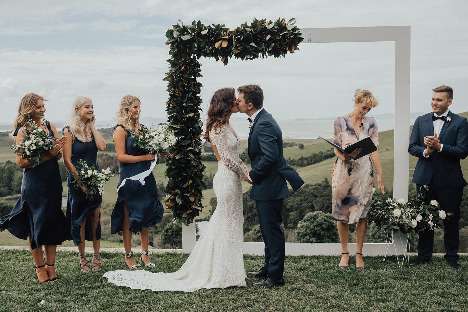 Real Weddings | Vinka Design | Real Brides Wearing Vinka Gowns | Nicole and Hayden kiss under arch at wedding ceremony