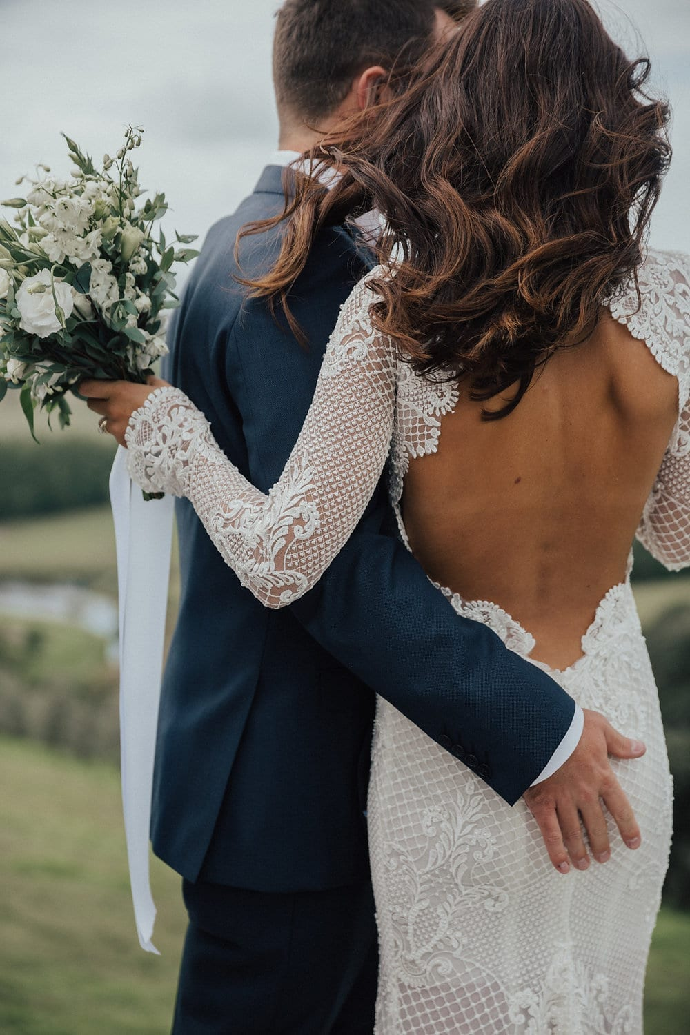 Real Weddings | Vinka Design | Real Brides Wearing Vinka Gowns | Nicole and Hayden close up of backs showing low back of dress and long sleeves