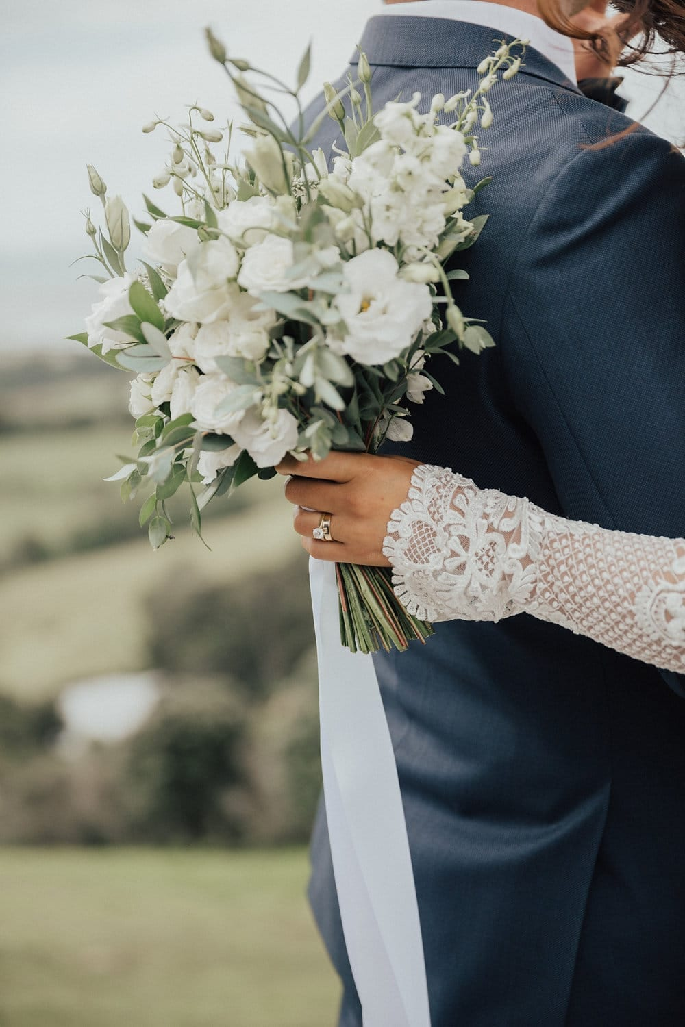 Real Weddings | Vinka Design | Real Brides Wearing Vinka Gowns | Nicole and Hayden close up Hayden's back with bouquet and long sleeve of dress
