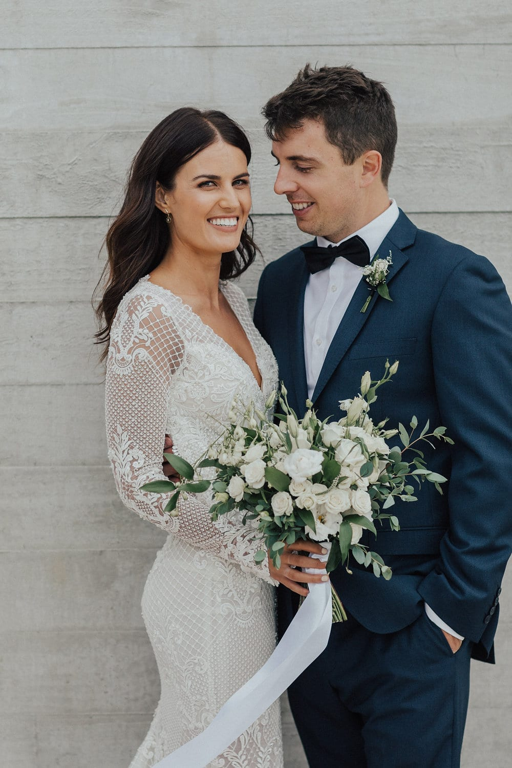 Real Weddings | Vinka Design | Real Brides Wearing Vinka Gowns | Nicole and Hayden close up smiling with custom dress v neck and detail