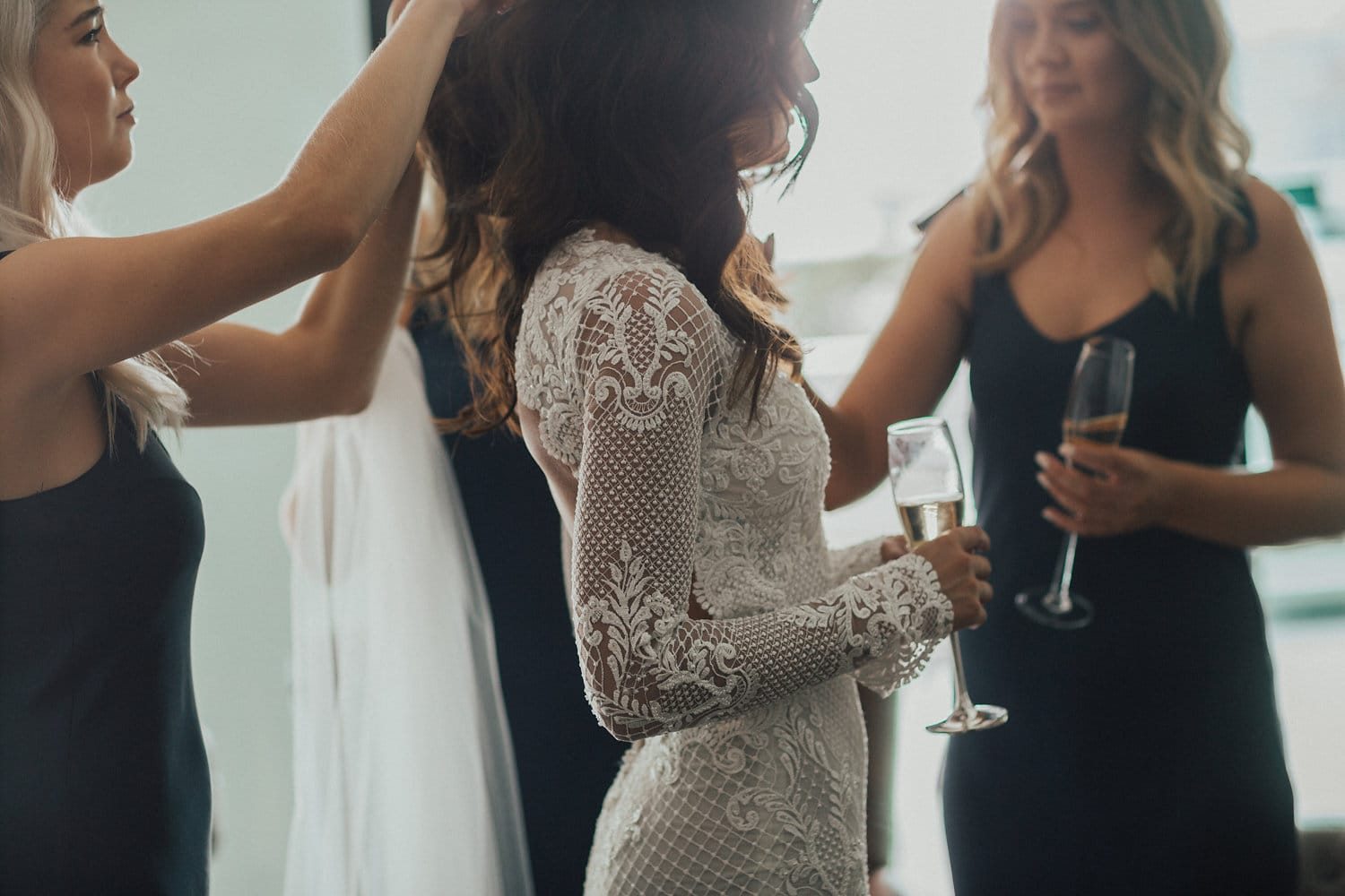 Real Weddings | Vinka Design | Real Brides Wearing Vinka Gowns | Nicole and Hayden - Nicole and bridesmaids attending to her veil close up showing stunning detail of long sleeves of bespoke dress