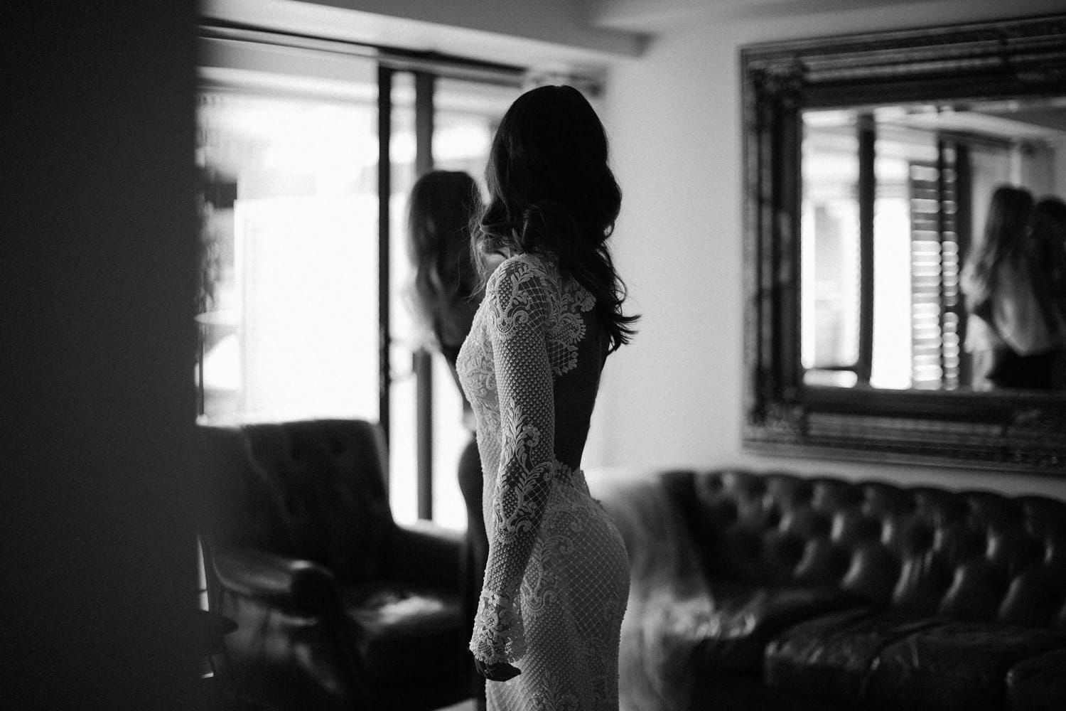 Real Weddings | Vinka Design | Real Brides Wearing Vinka Gowns | Nicole and Hayden - Nicole looking at back of bespoke dress in mirror in black and white