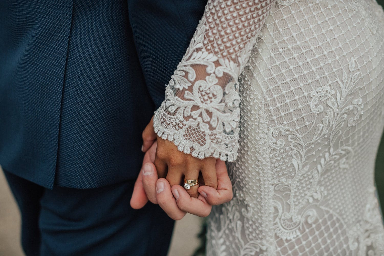 Real Weddings | Vinka Design | Real Brides Wearing Vinka Gowns | Nicole and Hayden close up of holding hands showing custom dress detail of long sleeves