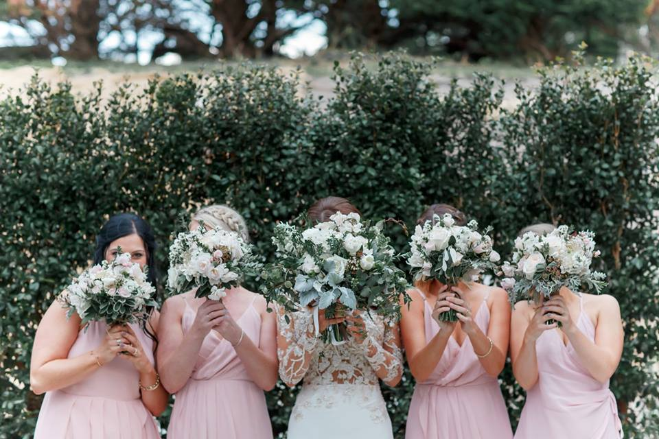 Real Weddings | Vinka Design | Real Brides Wearing Vinka Gowns | Haley and Mike - Haley and bridesmaids with bouquets in front of their faces