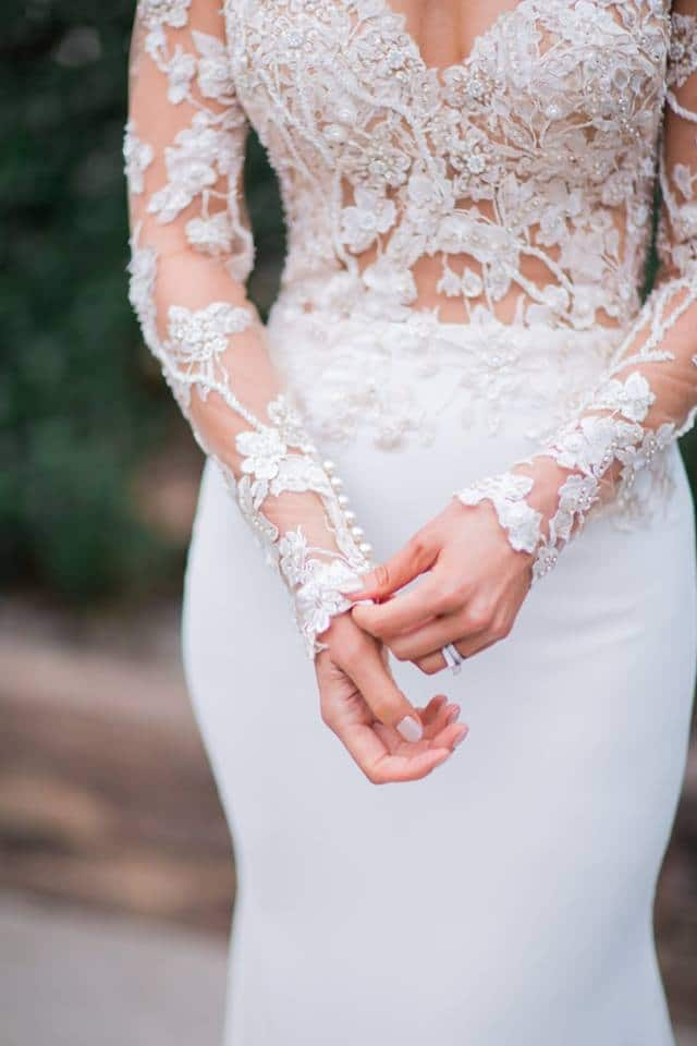 Real Weddings | Vinka Design | Real Brides Wearing Vinka Gowns | Haley and Mike - close up of lower half of bespoke dress with sheer bodice and lace embellishment and smooth fitted skirt