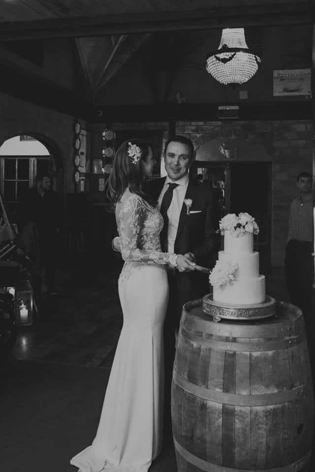 Real Weddings | Vinka Design | Real Brides Wearing Vinka Gowns | Haley and Mike cutting wedding cake
