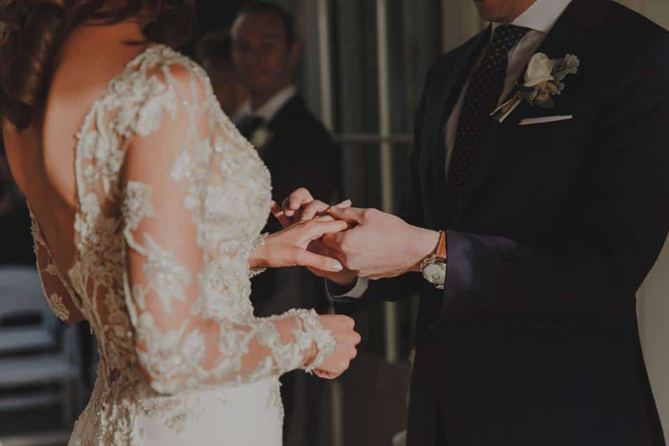Real Weddings | Vinka Design | Real Brides Wearing Vinka Gowns | Haley and Mike exchange rings close up of detail on long sleeves of bespoke wedding dress