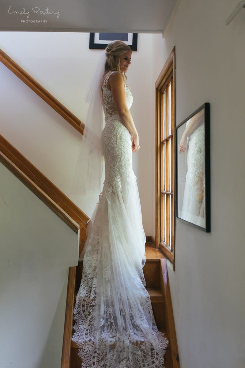 Real Weddings | Vinka Design | Real Brides Wearing Vinka Gowns | Kate and Graeme - Kate on stairs with dress train flowing down steps