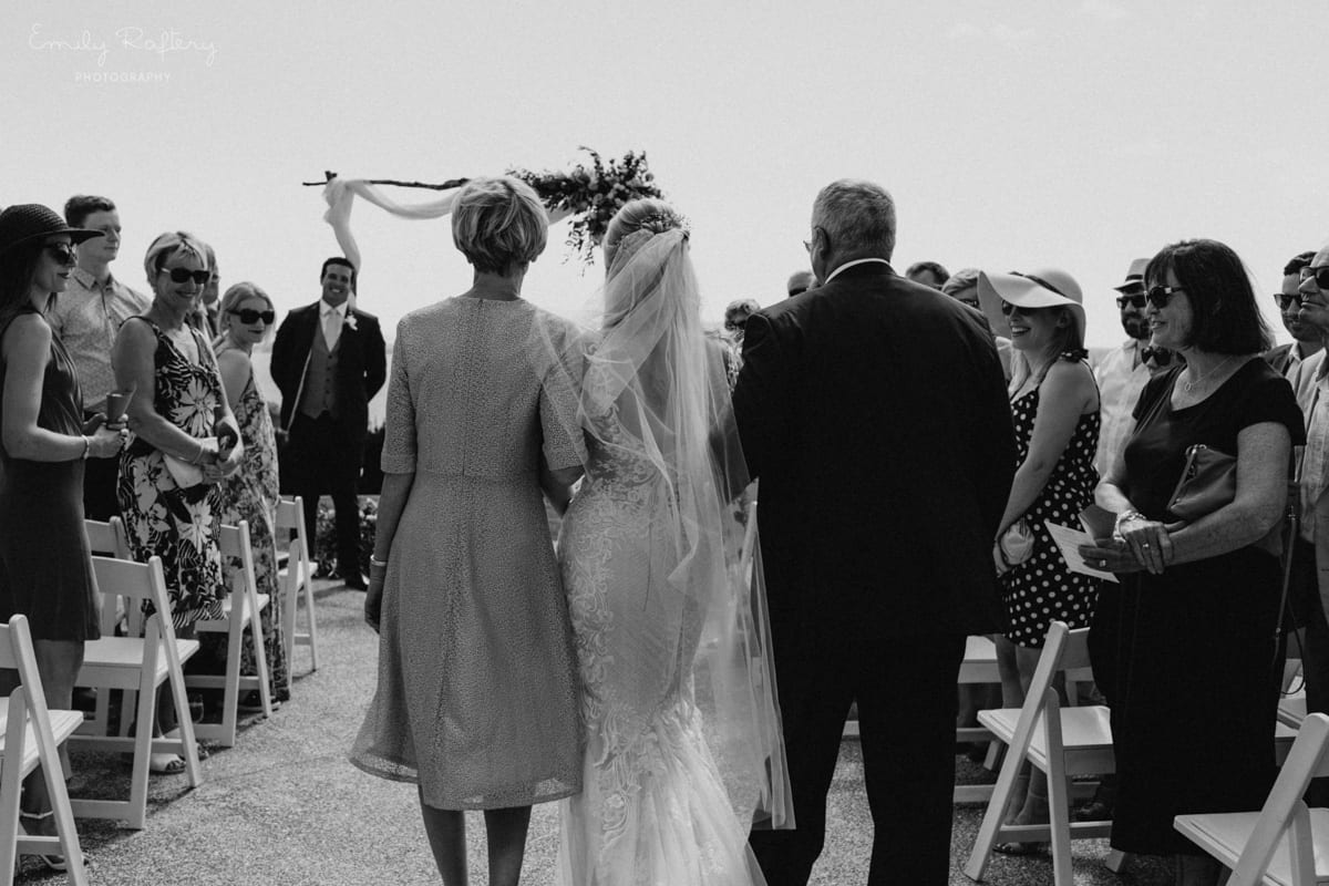 Real Weddings | Vinka Design | Real Brides Wearing Vinka Gowns | Kate and Graeme - Kate being walked up aisle showing back of custom made gown in lack and white