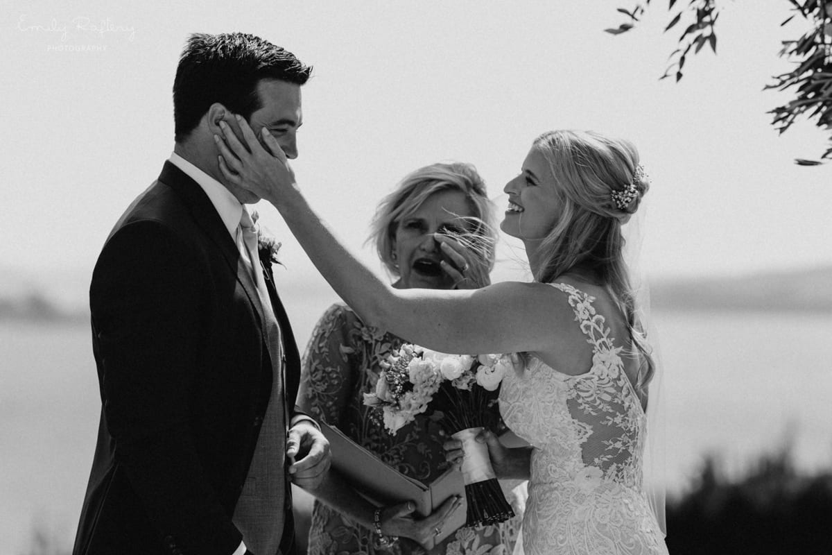 Real Weddings | Vinka Design | Real Brides Wearing Vinka Gowns | Kate and Graeme - Kate hand to Graeme's face with celebrant in background in black and white