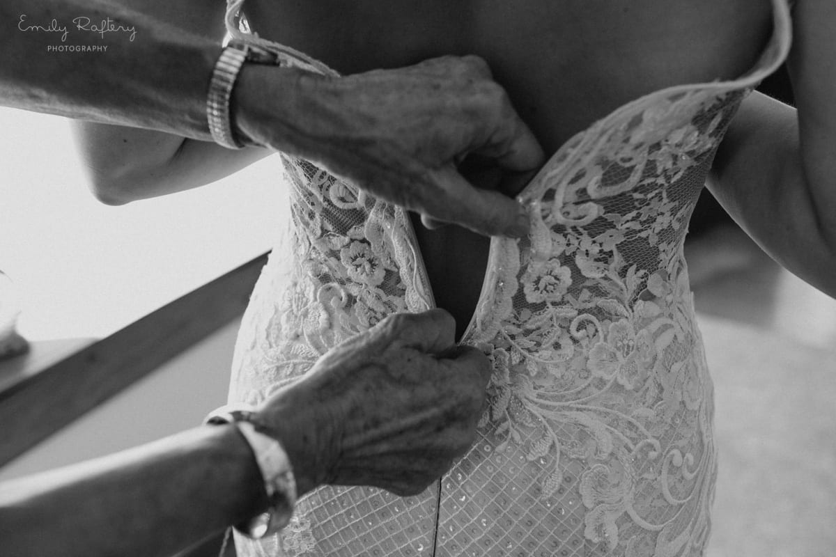 Real Weddings | Vinka Design | Real Brides Wearing Vinka Gowns | Kate and Graeme - Kate being zipped into custom made dress from back with lace embroidery detail