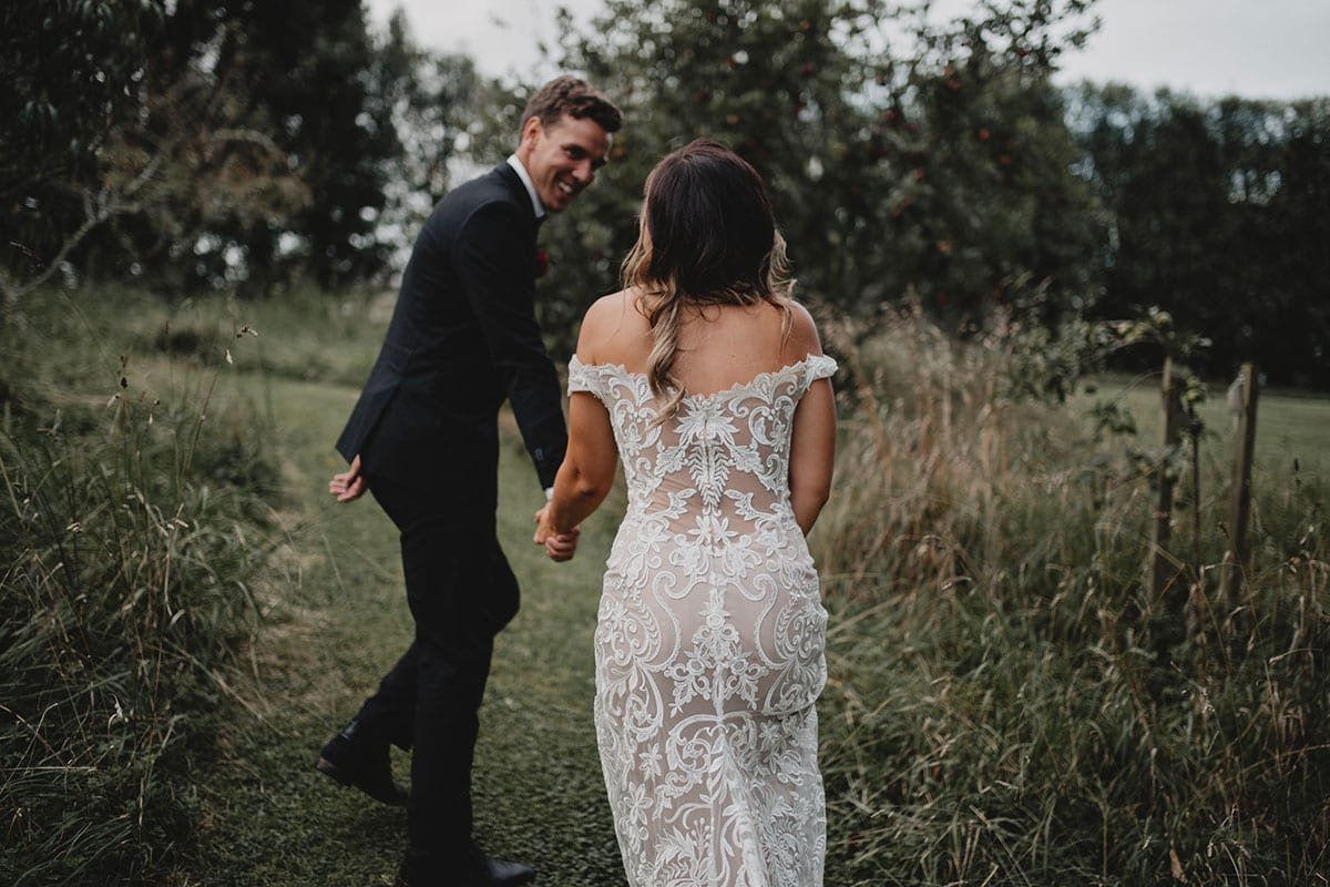 Real Weddings | Vinka Design | Real Brides Wearing Vinka Gowns | Amber and Rhys walking through field showing beautiful detail of back of custom made wedding dress