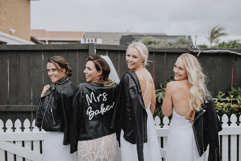 Real Weddings | Vinka Design | Real Brides Wearing Vinka Gowns | Amber and Rhys - bride and bridesmaids with leather jackets on their shoulders