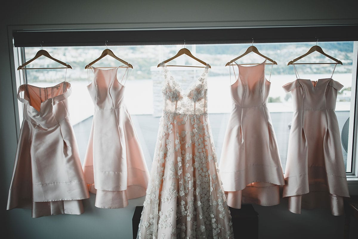 Real Weddings | Vinka Design | Real Brides Wearing Vinka Gowns | Megan and Tim - stunning custom made wedding dress hanging in the light of the window showing beautiful floral lace embellishments with bridesmaids dresses