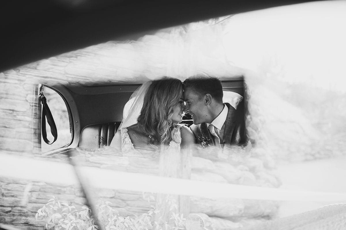 Real Weddings | Vinka Design | Real Brides Wearing Vinka Gowns | Megan and Tim in car rear view mirror in back of wedding car