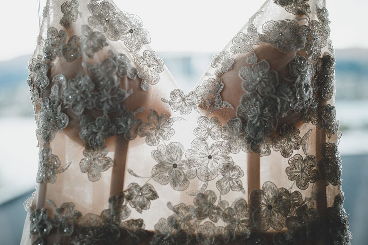Real Weddings | Vinka Design | Real Brides Wearing Vinka Gowns | Megan and Tim - stunning custom made wedding dress hanging in the light of the window showing beautiful floral lace embellishments