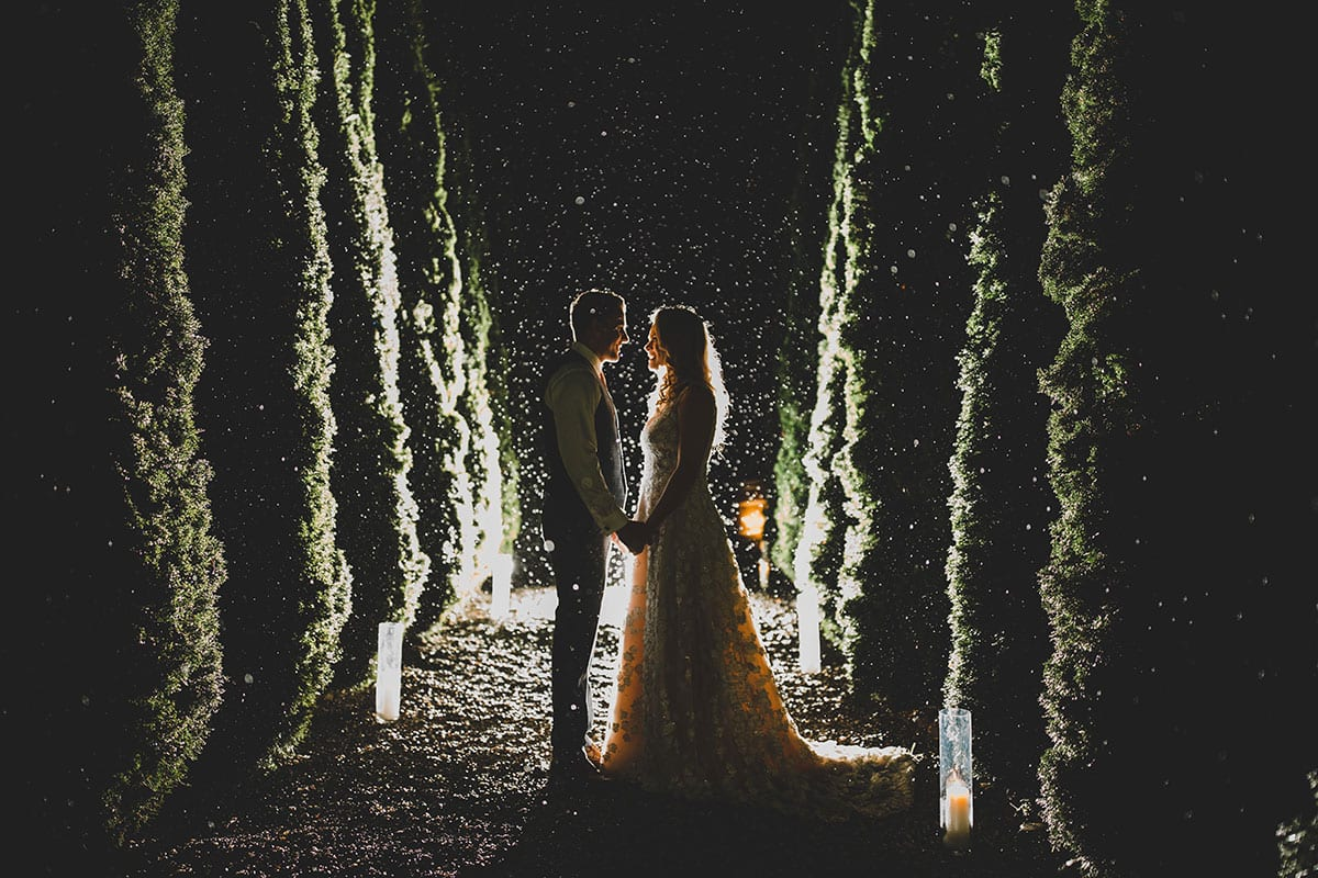 Real Weddings | Vinka Design | Real Brides Wearing Vinka Gowns | Megan and Tim at night time between tree lined path Megan in a custom made Vinka designer gown