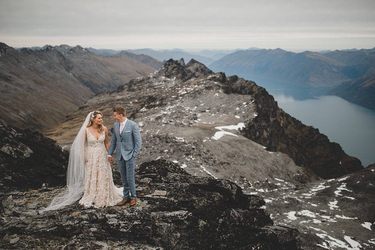 Real Weddings | Vinka Design | Real Brides Wearing Vinka Gowns | Megan and Tim walk along a mountain above Queenstown Megan's custom made dress standing out