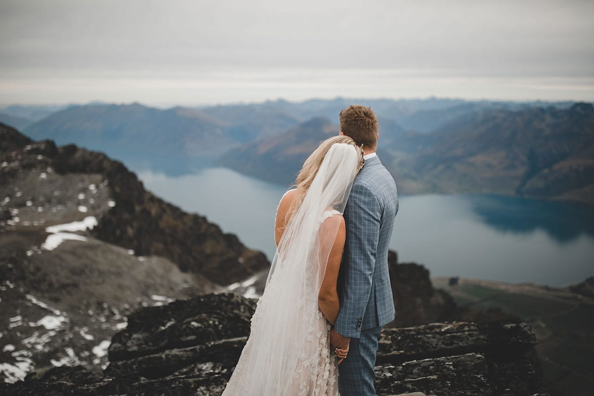 Real Weddings | Vinka Design | Real Brides Wearing Vinka Gowns | Megan and Tim look out across Queenstown from atop a mountain