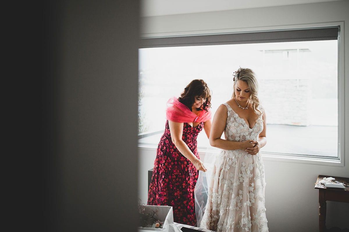 Real Weddings | Vinka Design | Real Brides Wearing Vinka Gowns | Megan and Tim - Megan being helped putting on dress showing low v neck