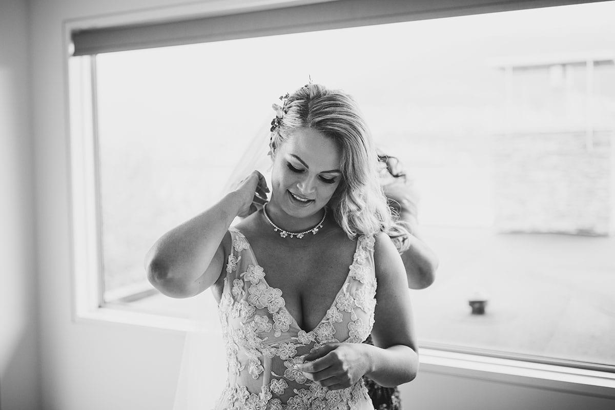 Real Weddings | Vinka Design | Real Brides Wearing Vinka Gowns | Megan and Tim - Megan having necklace put on top half showing custom made dress with low v neck