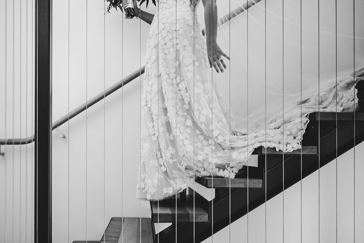 Real Weddings | Vinka Design | Real Brides Wearing Vinka Gowns | Megan and Tim - Megan walking down stairs showing bottom half of beautiful bespoke wedding dress