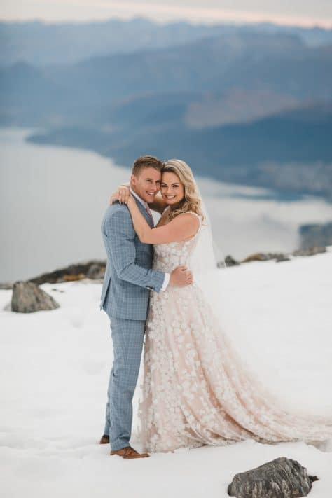 Real Weddings | Vinka Design | Real Brides Wearing Vinka Gowns | Megan and Tim together on a mountain top in Queenstown custom made dress train flowing behind Megan