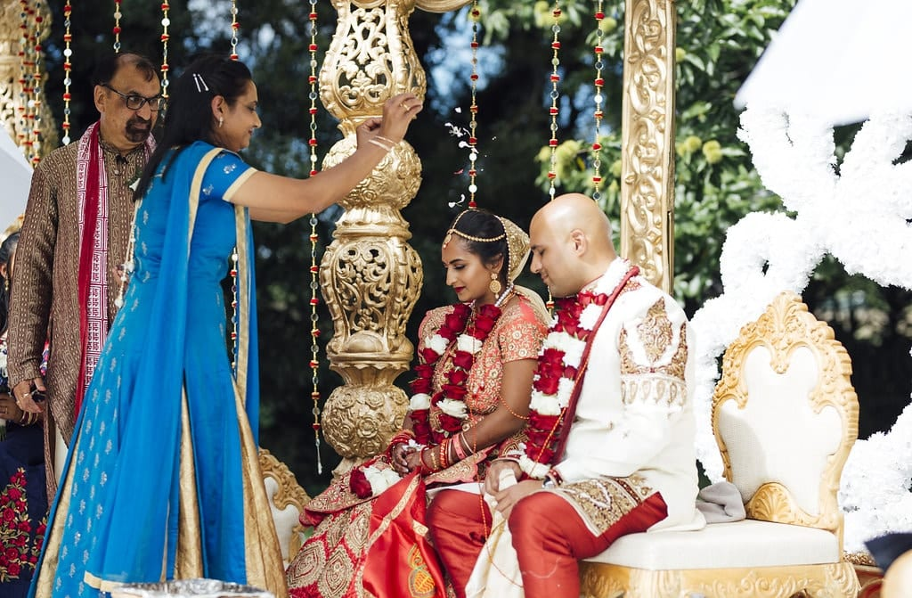 Real Weddings | Vinka Design | Real Brides Wearing Vinka Gowns | Shalini and Jayesh seated at Indian wedding ceremony