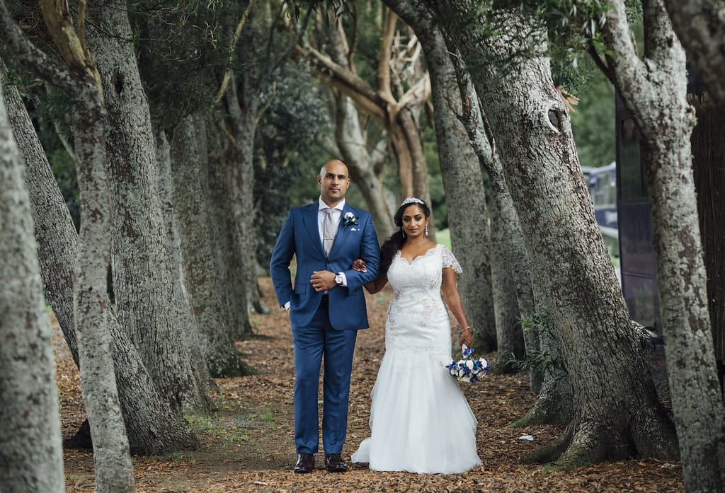 Real Weddings | Vinka Design | Real Brides Wearing Vinka Gowns | Shalini and Jayesh posing on pathway between trees Shalini in bespoke dress