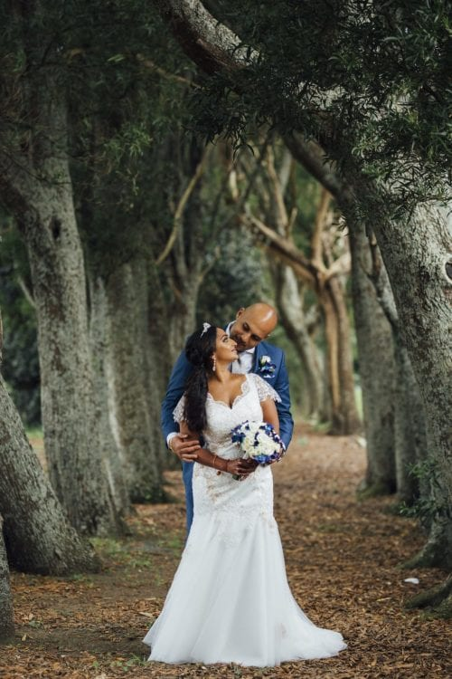 Real Weddings | Vinka Design | Real Brides Wearing Vinka Gowns | Shalini and Jayesh posing on pathway between trees with bespoke dress