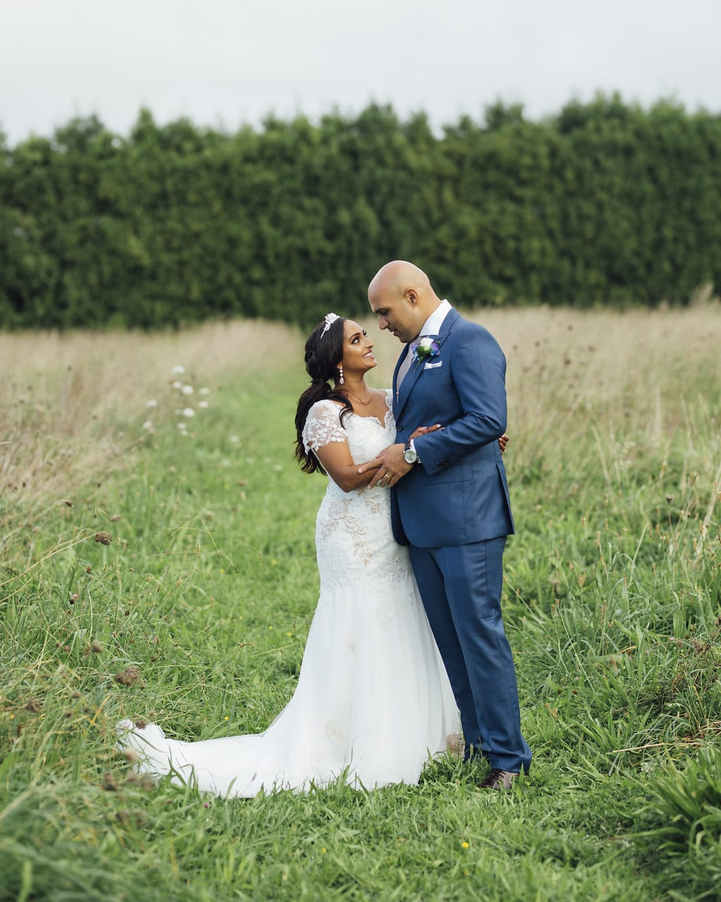 Real Weddings | Vinka Design | Real Brides Wearing Vinka Gowns | Shalini and Jayesh outdoor in open field face to face with train flowing to the side