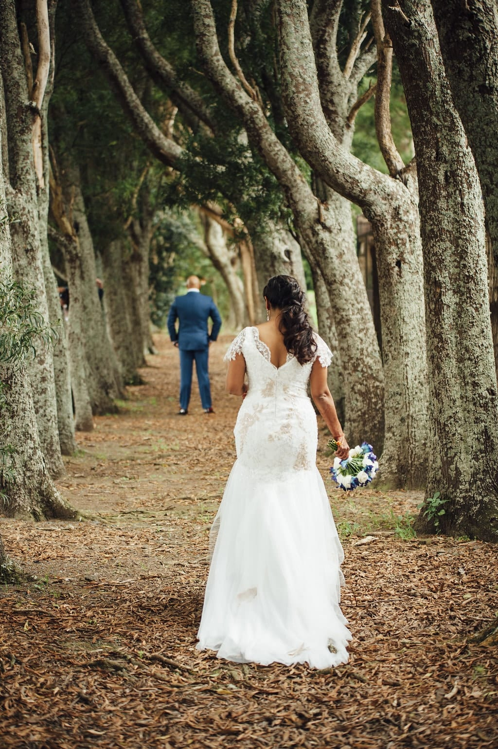 Real Weddings | Vinka Design | Real Brides Wearing Vinka Gowns | Shalini and Jayesh walking away through wooded path showing beautiful back of bespoke Vinka gown