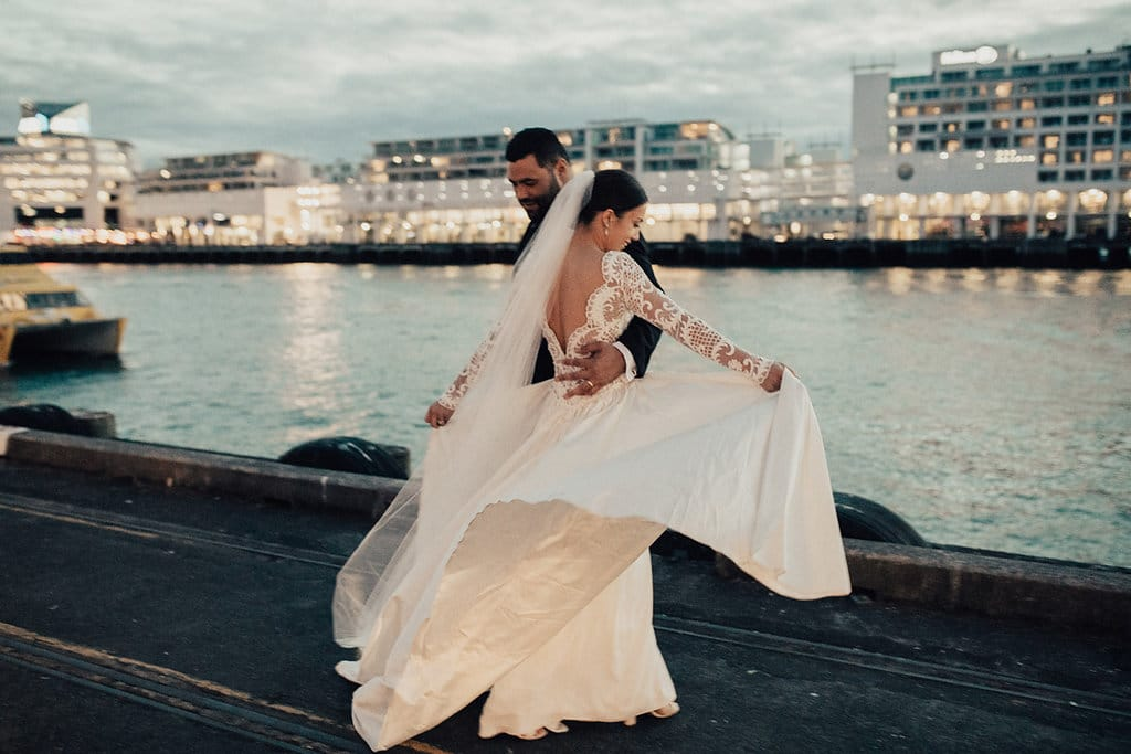 Real Weddings | Vinka Design | Real Brides Wearing Vinka Gowns | Olivia and Ben dancing on the harbour with Olivias beautiful silk train flowing