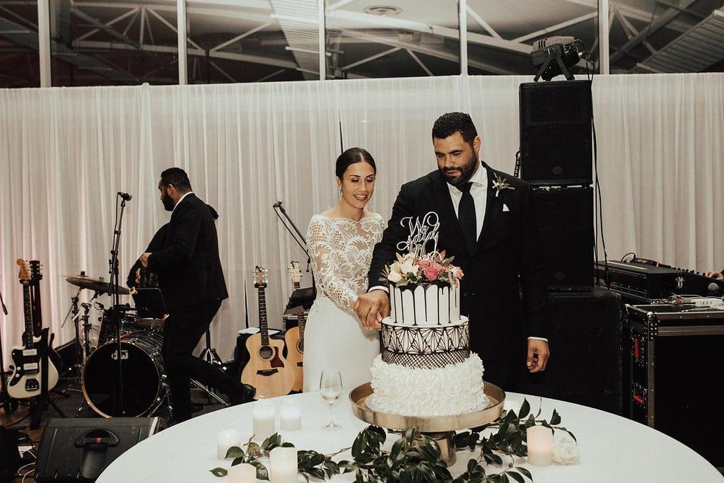 Real Weddings | Vinka Design | Real Brides Wearing Vinka Gowns | Olivia and Ben cutting wedding cake